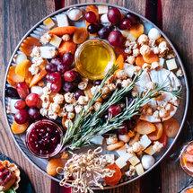 Поднос с сыром, виноградом, сушеными абрикосами и попкорном