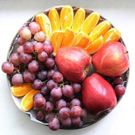 Поднос с апельсинами, яблоками и виноградом