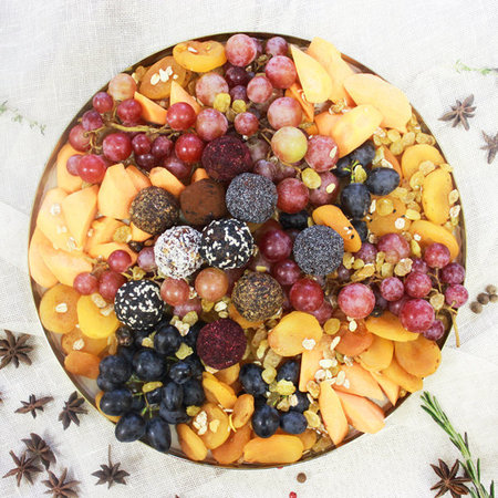Поднос с виноградом, конфетами из сухофруктов и морковью